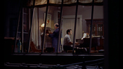 Rear Window (1954) - film frame - Film frame from ''Rear Window'' showing Hitchcock's cameo as a a clock winder in the musician's apartment.