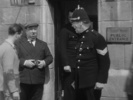 YOUNG AND INNOCENT (1937) - FILM FRAME - Film frame from ''Young and Innocent'' (1937) showing Hitchcock's cameo appearance as a photographer outside the police court.